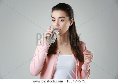 Beautiful young woman taking pill on light background