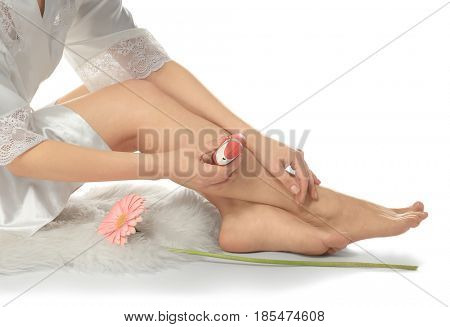 Woman sitting on rug and epilating legs on white background