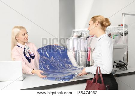 Female laundry worker with client on reception