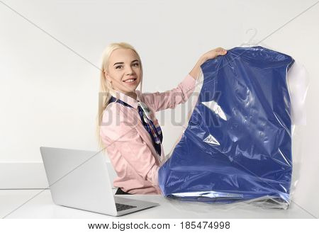 Female laundry worker holding clean clothes on reception