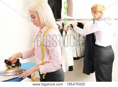 Female laundry worker ironing clothes in dry-cleaning