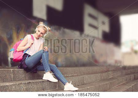 Beautiful girl listening music on street