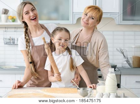 Young woman with mother and daughter cooking in kitchen