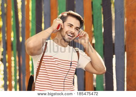 Handsome man with headphones listening music on colorful background