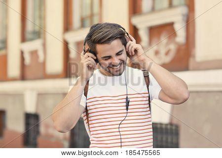 Handsome man with headphones listening music on street