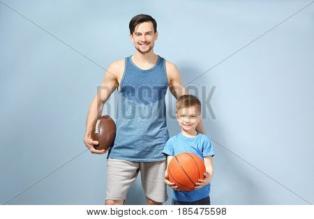 Father and son with balls on color background