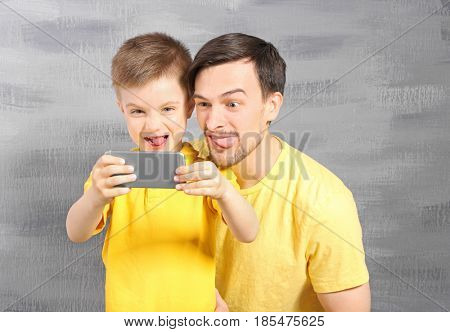 Handsome man and his son taking selfie near color wall