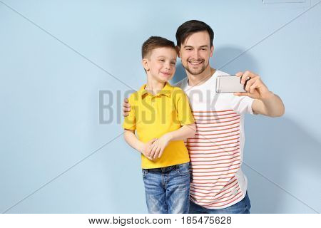 Handsome man and his son taking selfie on color background