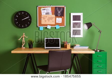 Comfortable work space near green wall