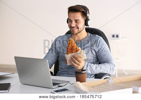 Young handsome man having a break and eating tasty pizza at office