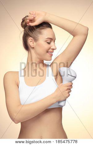 Beautiful young woman epilating armpits on light background