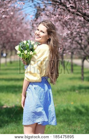 Young beautiful woman with bouquet of tulips in spring park
