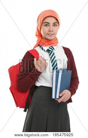 Cute girl with backpack and books on white background