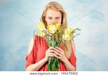 Beautiful young woman with bouquet of flowers on color background