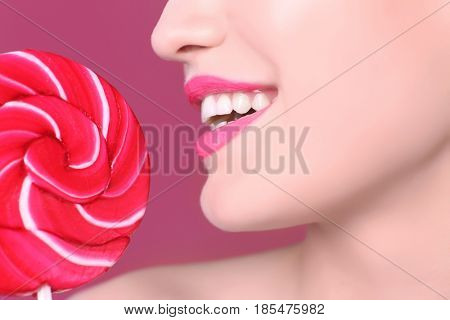 Face of beautiful young woman with lollipop on color background, closeup