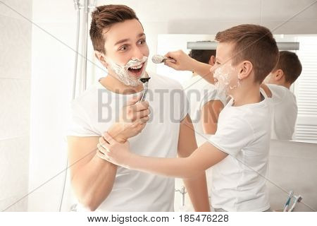 Father and son shaving in bathroom