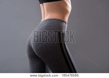 Perfect female buttocks of fitness girl isolated on grey background