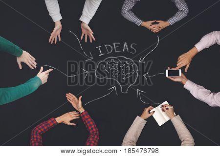 Teamwork concept - top view of six people generate ideas. Blackboard table.