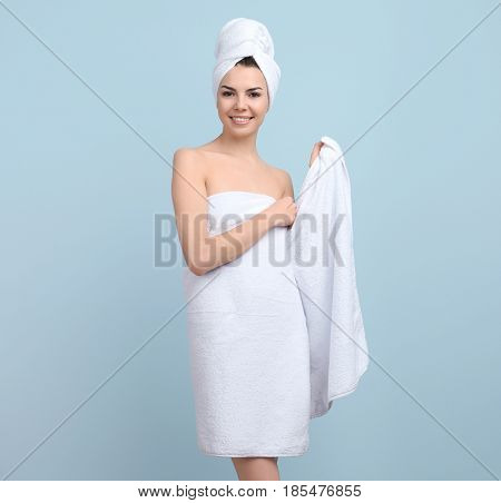 Beautiful young woman after shower on color background