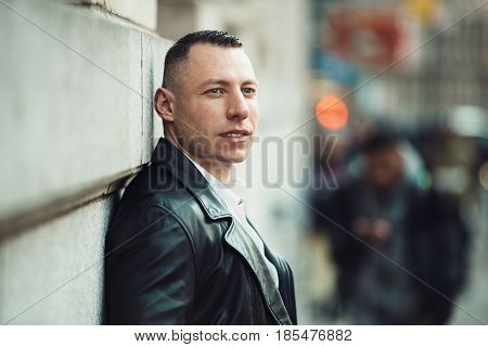 Adult businessman looking to the side and waiting for somebody in big city.