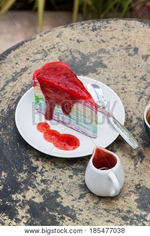 crape cake rainbow and hot espresso coffee in garden side home. crape cake with strawberry sauce