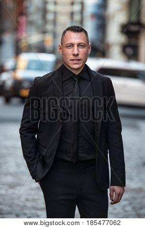 Close-up portrait of adult caucasian businessman on city street