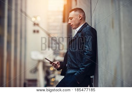 Adult businessman texting on mobile phone neat the wall on city street near office building.