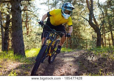 Professional Cyclist in Yellow T-shirt and Helmet Riding the Bike in the Forest. Extreme Sport Concept.