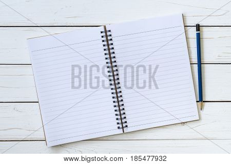 Open notebook with blank pages and pencil with space.