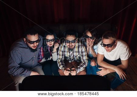 Scared and shocked five young friends in 3d glasses watch horror movie on tv at home, on couch.