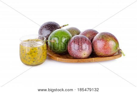 a glass of passion fruit juice with whole passion fruit in basket and on white background