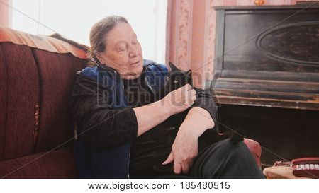 Portrait of happy old lady at home - senior woman sits on sofa with black cat - close up, telephoto