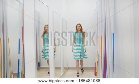 Attractive red hair girl chooses green dress near mirror in fitting room at store, middle shot