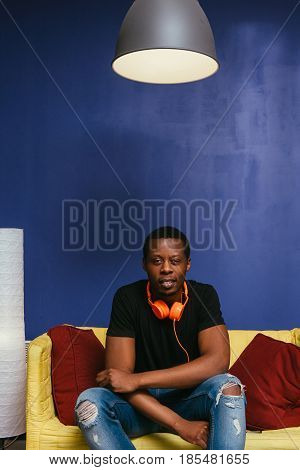 Young attractive black man sit on couch at home with orange headphones. Home leisure, pastime, lazy weekend , meloman, music concept.