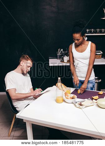 Young interracial family at home on kitchen. Cook together, write recipe, togetherness, weekdays and happy life concept. Free space on black background