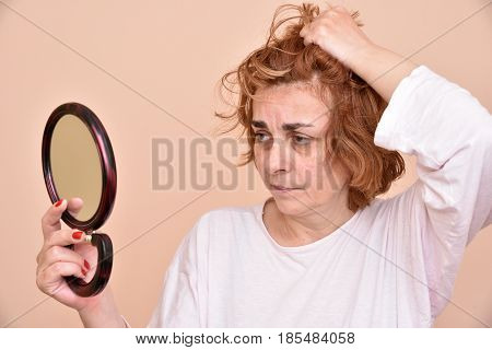 Unhappy and dissatisfied middle aged woman looking at her skin and unkempt hair in the mirror