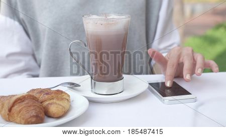 Young woman checks notifications on smartphone while drinking cacao with croissant. Female use mobile phone for business working during morning breakfast with hot chocolate. 4K