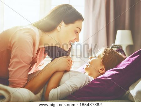 A nice girl and her mother enjoy sunny morning. Good time at home. Child sleeps. The mom wakes the kid on the bed in the bedroom.