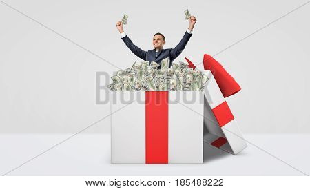 A happy businessman standing inside a large gift box full of dollar bills with his hands raised in victory motion. Business and profit. Investment and foreign exchange. Good fortune.
