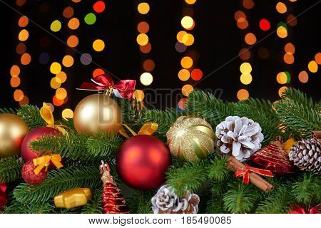 christmas decoration on white fur with fir tree branch closeup, gifts, xmas ball, cone and other object on dark background, lights and illumination, winter holiday concept