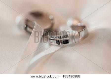 Wedding rings on a white satin pillow