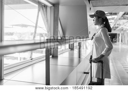 Woman traveler with bag luggage suitcase arrival at the airport during traveling travel trip for woman concept. Beautiful young tourist girl with carry on luggage in international airport. woman on airport. airport in Bangkok. girl in airport.