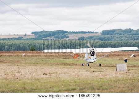 Bright scenic landscape with small propeller plane parked at the green grass in jungle. Sunny day. There are palms and trees on background. Selective focus on airplane. Borderless travel concept