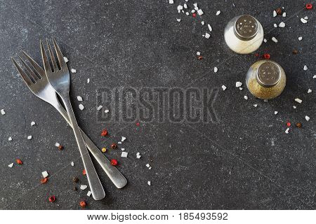 Grey abstract background with forks, salt and pepper shakers. Place for text