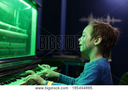 Child playing on light music piano at playground