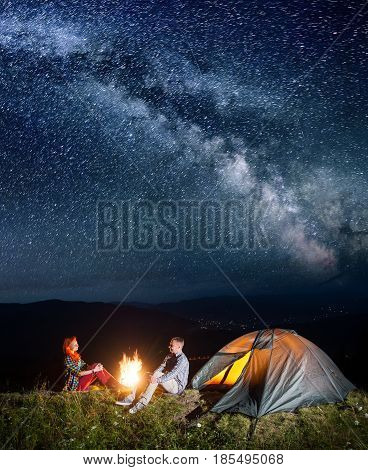 Night Camping. Happy Couple Backpackers Sitting By Bonfire And Tent Under Incredibly Beautiful Starr