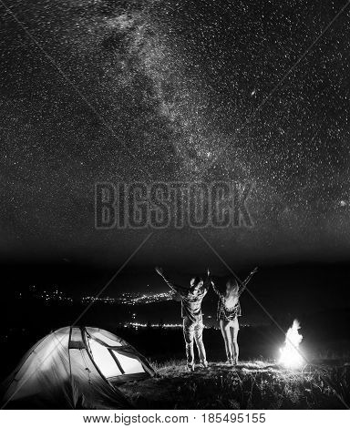 Happy Pair Tourists Raised Their Hands Up, Looking On The Beautiful Starry Sky At Night, Standing Ne