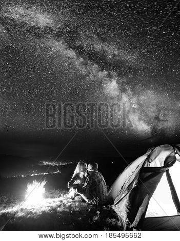 Night Camping. Tourist Family - Man And Woman Sitting And Kissing Near A Campfire And Tent Under The