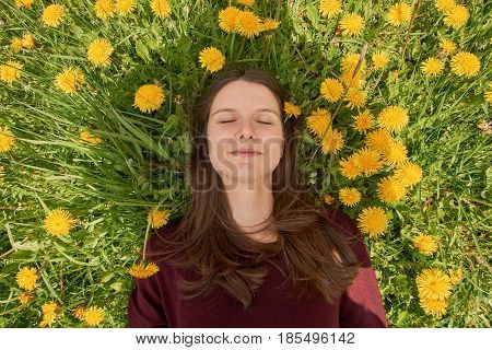 Beautiful young woman relaxing on a meadow with many dandelions in the spring sun. Lying between dandelions.
