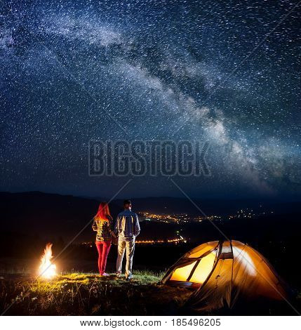 Happy Tourist Family - Man And Woman Holding Hands, Standing Near Campfire And Enjoying Starry Sky.